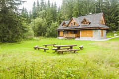 Cottage and a place to sit by the fire in the glade among the fo Stock Images