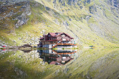 A cottage with reflection in mountain lake Royalty Free Stock Photos