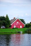Cottage by the river. Red wooden family house among trees and along a river, shot in village Minge, Lithuania Royalty Free Stock Photos