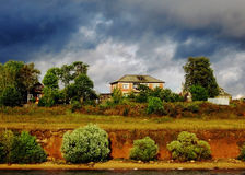 Cottage on river near green trees. Countryhouse in autumn, dramatic blue sky and clouds, surrounded by green trees and bushes, on the river Royalty Free Stock Images