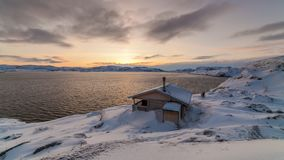Cottage on the shore of the Arctic Ocean at dawn in winter. Time Lapse stock footage