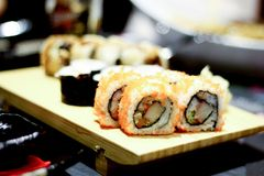 Sushi. Pieces presented on wooden plate Royalty Free Stock Image