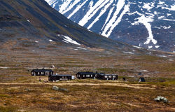 Cottage sotto una grande, montagna parzialmente nevosa Immagine Stock