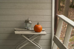 Cottage Still Life. Lantern and pumpkin on a table on a cottage porch, wooden wall on the background, copy space stock photos