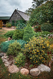 Cottage and stone wall with flowers Stock Image