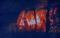 Cottage sur le feu la nuit Image stock