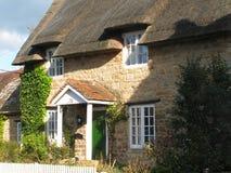 Cottage Thatched con una rete fissa di picchetto Immagini Stock