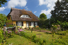 Cottage with thatched roof and pretty garden Royalty Free Stock Photography