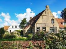 Cottage tipici sull'isola Ameland sotto un cielo blu fotografia stock libera da diritti
