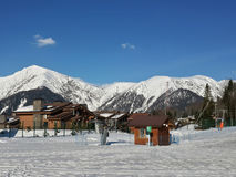 Cottage village at the foot of snow-capped Caucasus Mountains. Snowy Caucasus mountains, wooden cottages for rent, ski resort Krasnaya Polyana, Russia Royalty Free Stock Images