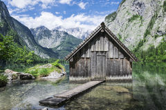 Cottage on the water. Between the mountains on a sunny day Royalty Free Stock Image