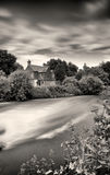 English cottage by a weir. Atmospheric black and white photo, taken, using a neutral density filter to slow the water and clouds down, producing a milky effect Royalty Free Stock Images