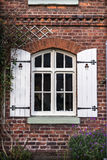 Cottage Window Shutters. Red brick cottage with wooden shutters and front garden Royalty Free Stock Photo
