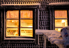 Cottage window with warm glow in Winter Royalty Free Stock Photos