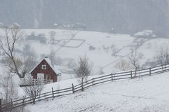 Cottage in winter. Sow falling over red cottage in the mountains Royalty Free Stock Images