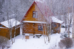 Cottage in winter. Small cottage during snowfall in Russian village Royalty Free Stock Image