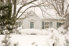 Cottage in winter snowstorm. House or small cottage covered by drifted snow during a heavy winter snowstorm Royalty Free Stock Image
