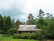 Cottage in the woods. Cloudy day Royalty Free Stock Photo
