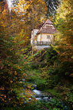 Cottage in the woods near a creek Stock Photography