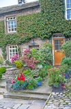 Cottage in Yorkshire Dales. Terraced cottage in Grassington Yorkshire Dales showing how tubs of flowers along the path add color to the house stock photos