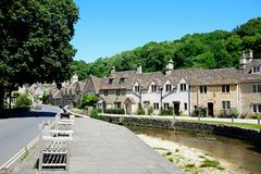 Cottages alongside the river, Castle Comble. Stone cottages alongside the river Bybrook with wooden benches in the foreground, Castle Combe, Wiltshire, England royalty free stock photo