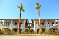 Cottages with balcony and garden with palm trees Royalty Free Stock Image