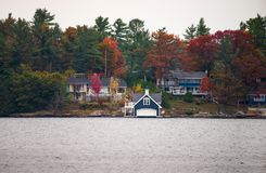 Cottages and a boathouse on a lake Stock Photos