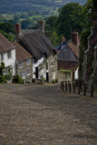 Cottages on a country lane. A row of cottages lined up down a very steep country lane. The street is cobblestoned, and has a handrail on the right side of the Stock Photo