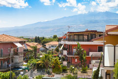 Cottages in Giardini Naxos city and view of Etna. Travel to Sicily, Italy - cottages on street via ischia in Giardini Naxos city and view of Etna Mount in summer Royalty Free Stock Photo