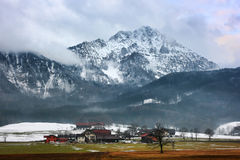 Cottages and snowy peak. Royalty Free Stock Image