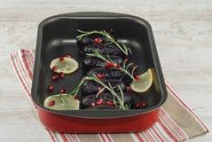 Cotto in di sanguinaccio del forno in piatto bollente con il limone ed i rosmarini fotografia stock