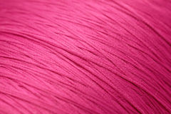 Cotton. Macro close-up of fine pink cotton wound round spool Royalty Free Stock Images