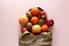 Cotton bag with different fruits on pink background. Ecology pack for free plastic shopping. Top view. Flat lay.  stock photos