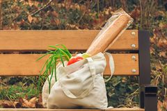 A cotton bag full of fresh, natural vegetables on a wooden surface .the concept of recycling ,the freedom from plastic.  stock photography