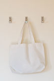 Cotton Bag. White cotton bag hanging on the wall stock image