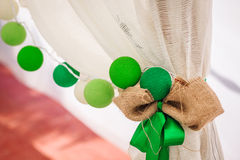 Cotton balls garland hangs on a white curtain. Bright colored decoration. Wedding. Outdoors Stock Photography