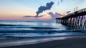 Dramatic sunrise lights up the clouds and pastel colors light up the clouds. An old wooden ocean pier at sunrise. royalty free stock photos