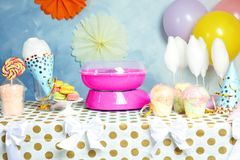 Cotton candy machine and treats on table. At party royalty free stock photos