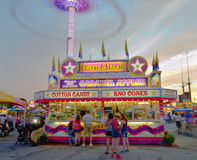 Cotton Candy Stand. People placing orders at a confection stand in a carnival setting, at sunset, with the lights from rides spinning in the background Stock Images