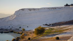 Cotton Castle in Pamukkale Turkey during sunset. Panoramic view of Cotton Castle in Pamukkale Turkey, walking people on the background stock video