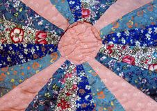 Cotton Craft. This quilt coverlet has a wheel shaped design made up of blue print squares with a pink patterned center and spokes Stock Photo
