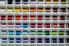 Cotton display. Display rack of brightly coloured cotton reels; differential focus Stock Images
