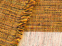 Cotton fabric blended of orange, black, yellow and white, folded with fringes. Close-up of handmade ruddy cotton fabric blended of orange, black, yellow and Stock Photography