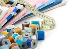 Cotton fabric material, tailor measurement tape and spools of co Royalty Free Stock Images