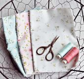 Patterned fabrics. Cotton flowered fabrics, thread and scissors in the wire basket stock photos