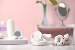 Cotton flowers and pads on table in bathroom. Space for text stock image
