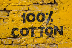 100% cotton. Painting on the wall with yellow background Royalty Free Stock Photo