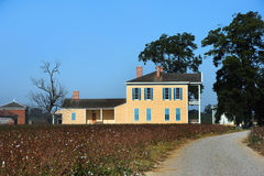 Cotton Plantation Lakeport. Road leads to Lakeport Plantation in the Mississippi Delta area of Arkansas. Two story home is wooden and painted yellow with blue royalty free stock image