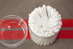 Cotton in plastic boxes. Cotton buds in transparent plastic box on a shirt background stock photography