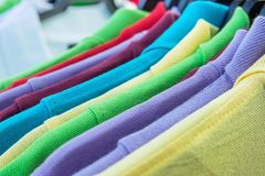 Cotton Polo Shirts of Various Colors Blue Yellow Red Purple Green White Hanging on Hangers on Rack in Clothing Store. Sales Retail. Consumerism Fashion Casual royalty free stock photography